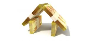Stacks of two hundred rand bank notes assembled in the shape of a house on an isolated background
